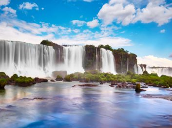Iguazu waterfalls in Argentina, view from Devil's Mouth. Panoramic view of many majestic powerful water cascades with mist. Panoramic image with reflection of blue sky with clouds.